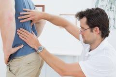 La vista lateral de un fisioterapeuta de sexo masculino que examina sirve detrás foto de archivo