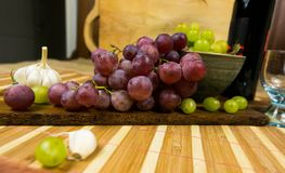 La vista lateral de un moscatel rojo y amarillo coloreó la uva, la botella de vino, el ajo y un vidrio en un tablero de madera -  Fotografía de archivo