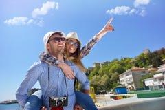 La vista lateral de un par de 2 turistas con una relajación que se sienta de la maleta y el goce vacations en una 'promenade' col Fotografía de archivo libre de regalías
