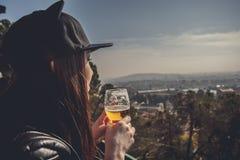 La vista lateral de una mujer joven vistió el alcohol derecho y de consumición Fotografía de archivo