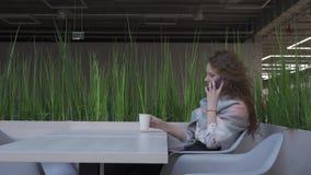La vista lateral de una mujer joven y bonita con el pelo rojo que se está sentando en un café coge el teléfono almacen de metraje de vídeo