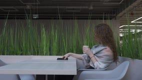 La vista lateral de una mujer joven y bonita con el pelo rojo que se está sentando en un café coge el teléfono metrajes