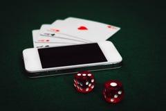 La vista lateral de una tabla verde del póker con un smartphone, carda y corta en cuadritos Apego en línea de juego del app foto de archivo