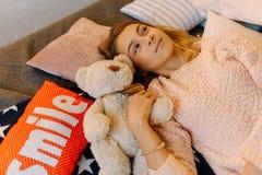La vista lateral del adolescente de sueño que miente con el peluche refiere las almohadas Foto de archivo