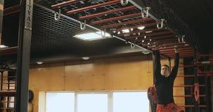 La vista lateral del culturista chinning para arriba en la barra, entrenamiento del hombre en la elaboración del gimnasio es cuer metrajes