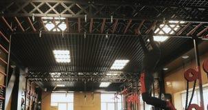 La vista lateral del culturista chinning para arriba en la barra, entrenamiento del hombre en la elaboración del gimnasio es cuer almacen de metraje de vídeo
