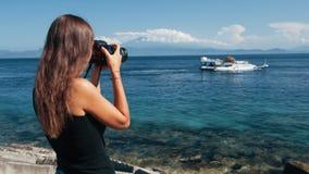 La vista lateral del fotógrafo de la muchacha hace la foto del barco en cámara profesional almacen de metraje de vídeo