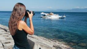La vista lateral del fotógrafo de la muchacha toma imágenes del barco en cámara profesional metrajes