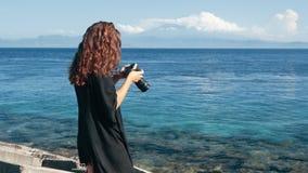 La vista lateral del fotógrafo de la muchacha toma imágenes del océano y de montañas almacen de video