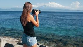 La vista lateral del fotógrafo turístico de la muchacha toma imágenes del océano y de montañas metrajes