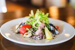 La vista lateral del primer de la ensalada hecha de los mariscos tales como mejillones, pulpo, lechuga, tomates, limón y cebolla Fotografía de archivo