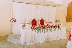 La vista lateral del sistema de lujo de la tabla de la boda adornado con las rosas rojas y blancas Fotos de archivo