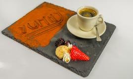 La vista lateral sobre el café en una taza da fruto y la palabra deliciosa en negro Foto de archivo libre de regalías