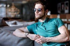 La vista lateral tiró de pensar al hombre atractivo sin afeitar en las gafas de sol que se basaban sobre el sofá Fotos de archivo