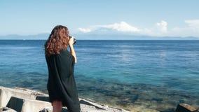 La vista lateral trasera del fotógrafo de la muchacha toma las imágenes del océano, montañas, cámara lenta metrajes