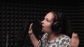 La vista laterale alta vicina della ragazza impulsivo sta cantando al microfono Canto drammatico Ripetizione di registrazione pro stock footage