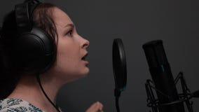 La vista laterale alta vicina della ragazza sveglia in cuffie sta cantando la canzone Canto drammatico emozionale Studio vocale p stock footage