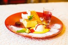 La vista laterale del dessert ha consistito dell'ananas, dei dolci, della menta, della gelatina e di una tazza del succo La compo immagini stock