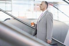 La vista laterale del mezzo ha invecchiato l'uomo d'affari con la tazza di caffè che cammina sulle scale nella stazione ferroviar Fotografia Stock