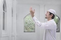 La vista laterale dell'uomo musulmano asiatico con il vestito tradizionale prega Fotografie Stock Libere da Diritti