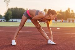 La vista laterale della donna atletica che risolve nello stadio, piegante ed allungante la sua indietro gamba muscles Fotografie Stock Libere da Diritti