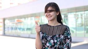 La vista laterale della ragazza felice attraente sta mostrando come alla città archivi video