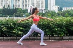 La vista laterale di addestramento dell'atleta femminile che fa l'affondo si esercita con l'aria aperta stesa delle mani nel parc Fotografia Stock Libera da Diritti