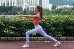 La vista laterale di addestramento dell'atleta femminile che fa l'affondo si esercita con l'aria aperta stesa delle mani nel parc Immagini Stock Libere da Diritti