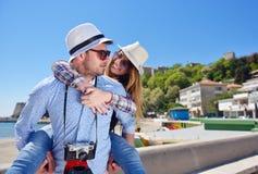 La vista laterale di una coppia di 2 turisti con un rilassamento di seduta della valigia e godere vacations in una passeggiata va Immagini Stock Libere da Diritti