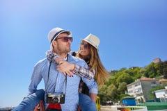 La vista laterale di una coppia di 2 turisti con un rilassamento di seduta della valigia e godere vacations in una passeggiata va Immagine Stock Libera da Diritti