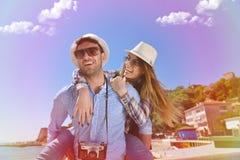 La vista laterale di una coppia di 2 turisti con un rilassamento di seduta della valigia e godere vacations in una passeggiata va Fotografia Stock Libera da Diritti