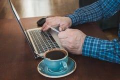 La vista laterale ha sparato delle mani del ` una s dell'uomo che tengono la carta e che per mezzo del computer portatile che si  Immagini Stock Libere da Diritti