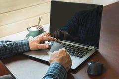 La vista laterale ha sparato delle mani del ` una s dell'uomo che tengono la carta e che utilizzano il computer portatile che si  Immagine Stock