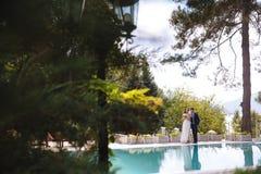 La vista lontano dalla sposa e dallo sposo passeggia intorno all'hotel, chiacchierante insieme e spendente il tempo sul loro gior Immagine Stock Libera da Diritti