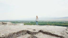 La vista magnifica nella Georgia dal bordo della scogliera, ragazza con capelli volanti biondi in vestiti luminosi dell'estate st video d archivio