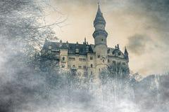 La vista meravigliosa del castello del Neuschwanstein nelle alpi della Baviera dal ponte ha perso nella nebbia con le nuvole Fotografia Stock