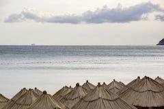 La vista panorámica del mar de la tarde, de la nube grande hermosa, la nave en la distancia y es muchos paraguas de la paja Fotos de archivo libres de regalías
