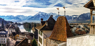 La vista panorámica hermosa de los tejados viejos de la ciudad de Thun y las montañas encendido apoyan Imagen de archivo libre de regalías