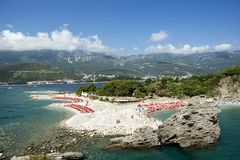 La vista panorámica hermosa de la playa con un gran número de calesa roja brillante gandulea, las altas montañas de Montenegro Imagenes de archivo