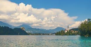 La vista panoramica del lago ha sanguinato con il castello sulla scogliera e la chiesa sull'isola Fotografia Stock