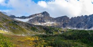 La vista panoramica del paesaggio di neve ha ricoperto le montagne e gli alberi di colore di autunno fotografia stock