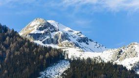 La vista panoramica del paese delle meraviglie idilliaco dell'inverno con la montagna completa nelle alpi un giorno soleggiato co Immagine Stock Libera da Diritti