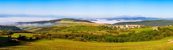 La vista panoramica del villaggio, dei prati e della montagna tradizionali ha suonato Immagine Stock Libera da Diritti
