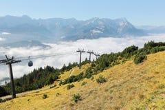 La vista panoramica della montagna Zugspitze dalla cima del supporto Wank con una cabina di funivia che scivola sopra il mare del Fotografie Stock