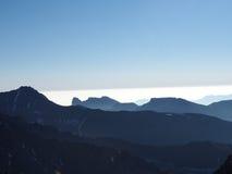 La vista panoramica delle colline e delle montagne con molte gamme fumose nebbiose impilate ha evidenziato indietro il sole legge Fotografia Stock Libera da Diritti