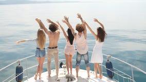 La vista posterior de amigos celebra en el velero en el océano, brazos aumentados almacen de metraje de vídeo