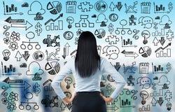 La vista posterior de la señora del negocio y los iconos del negocio se dibujan en la pantalla de cristal Imagen de archivo