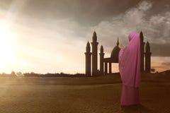 La vista posterior de la mujer musulmán asiática con velo ruega a dios Foto de archivo