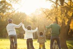La vista posterior de una familia joven con los brazos aumentó en la bici Foto de archivo