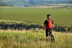 La vista posterior del deportista con su bici de montaña se coloca en el prado y la mirada lejos en el campo Fotos de archivo libres de regalías